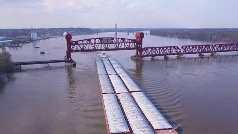 A-beautiful-aerial-of-a-barge-traveling-under-a-steel-drawbridge-on-the-Mississippi-River-1