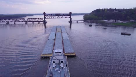 A-beautiful-vista-aérea-of-a-barge-traveling-on-the-Mississippi-Río-towards-a-large-steel-drawbridge