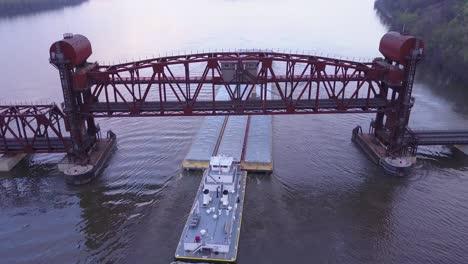 Una-Hermosa-Antena-De-Una-Barcaza-Viajando-Por-El-Río-Mississippi-Bajo-Un-Gran-Puente-Levadizo-De-Acero