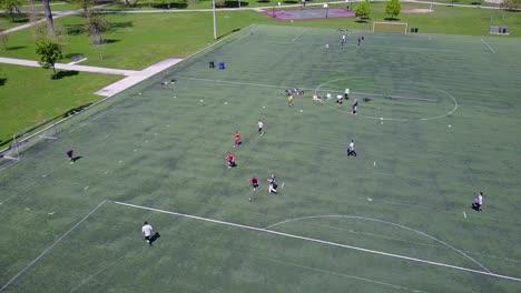 Toma-Aérea-Sobre-Un-Partido-De-Fútbol-Amateur-En-Un-Campo-De-Fútbol