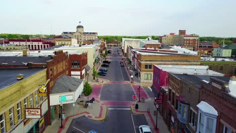 A-lovely-aerial-over-a-Main-Street-in-small-town-USA-ends-with-two-kids-skateboarding-down-the-empty-boulevard