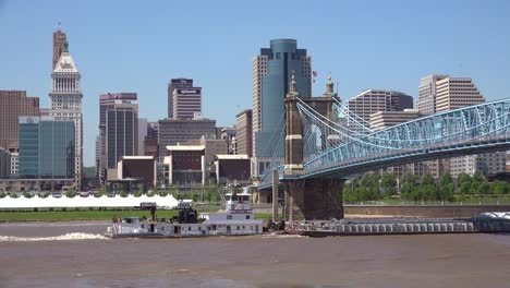 An-establishing-shot-of-Cincinnati-Ohio-with-a-barge-on-the-Ohio-River