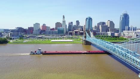 Una-Gran-Toma-Aérea-De-Cincinnati-Ohio-Con-Puente-Con-Una-Barcaza-En-El-Río-Ohio