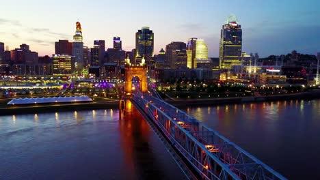 Una-Hermosa-Toma-Aérea-De-La-Noche-De-Cincinnati-Ohio-Con-El-Puente-Que-Cruza-El-Río-Ohio-En-Primer-Plano-11