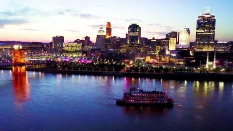 A-beautiful-evening-aerial-shot-of-Cincinnati-Ohio-with-riverboat-and-bridge-crossing-the-Ohio-River-foreground