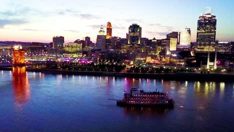 A-beautiful-evening-vista-aérea-shot-of-Cincinnati-Ohio-with-riverboat-and-bridge-crossing-the-Ohio-Río-foreground