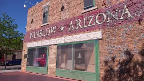 Establishing-shot-of-downtown-Winslow-Arizona-with-mural-depicting-a-flatbed-Ford