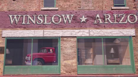 Establishing-shot-of-downtown-Winslow-Arizona-with-mural-depicting-a-flatbed-Ford-1
