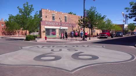 Establishing-shot-of-downtown-Winslow-Arizona-with-mural-depicting-a-flatbed-Ford-and-Route-66-sign
