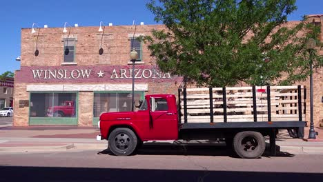 Establishing-shot-of-downtown-Winslow-Arizona-with-mural-depicting-a-flatbed-Ford-on-Route-66