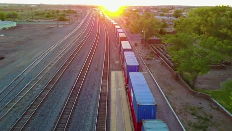 High-aerial-over-a-freight-train-full-of-containers-for-export-heading-into-the-sunset-1