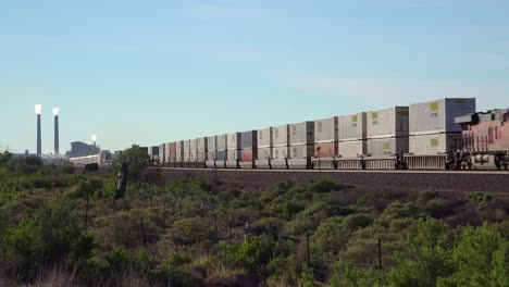 A-freight-train-heads-across-the-desert-with-an-industrial-site-background