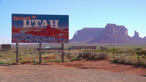 A-sign-welcomes-visitors-to-Utah-with-Monument-Valley-background