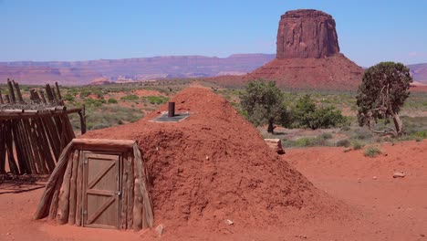 Traditional-Navajo-tribal-house-with-peaks-of-Monument-Valley-background
