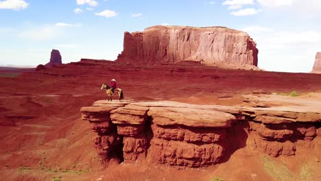 Remarkable-aerial-over-a-cowboy-on-horseback-overlooking-Monument-Valley-Utah