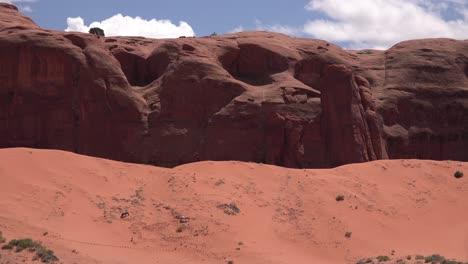 Horses-graze-in-the-distance-against-desert-cliffs