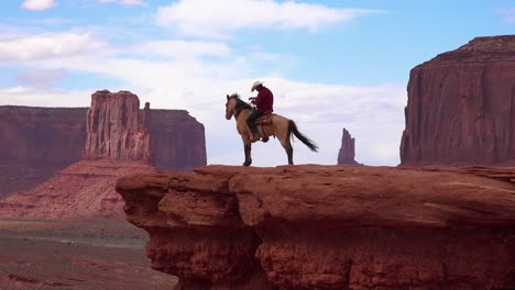 A-cowboy-sits-on-a-horse-on-a-cliff-in-Monument-Valley-Utah