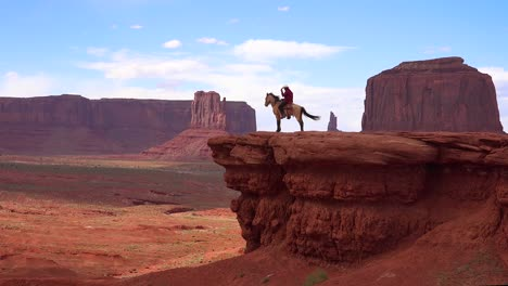 A-cowboy-sits-on-a-horse-on-a-cliff-in-Monument-Valley-Utah-1