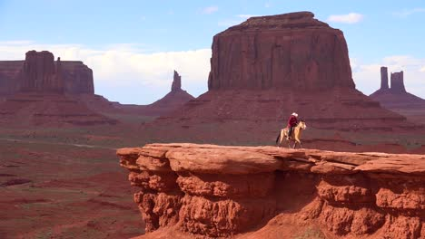 A-cowboy-sits-on-a-horse-on-a-cliff-in-Monument-Valley-Utah-2