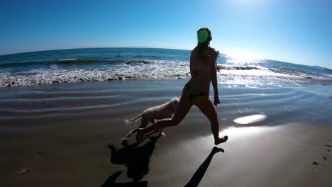 A-girl-runs-with-her-dog-on-the-beach-in-slow-motion