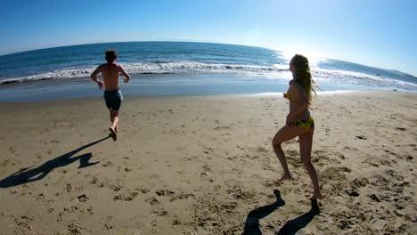 Un-Joven-Feliz-Y-Una-Mujer-Corren-Por-La-Playa-En-Cámara-Lenta-Y-Hacia-El-Océano