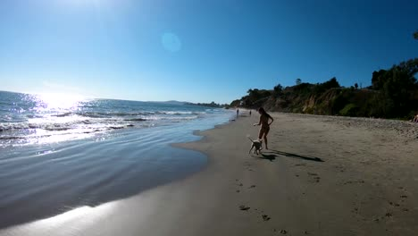 A-girl-runs-with-her-dog-on-the-beach-in-slow-motion-1