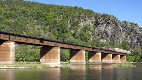 A-freight-train-travels-over-a-bridge-loaded-with-cargo-in-West-Virginia