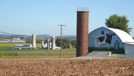 Establecimiento-De-Tiro-De-Una-Granja-Lechera-Con-Gran-Vaca-Pintada-En-El-Granero