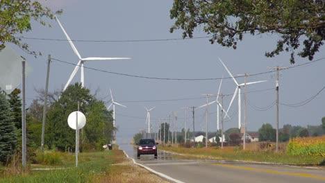 Cars-travel-on-a-highway-near-a-massive-wind-turbine-farm-producing-alternative-energy