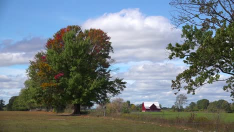 A-red-barn-stands-in-a-farm-field-as-the-seasons-change