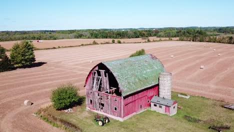 An-aerial-shot-goes-around-a-barn-on-a-farm
