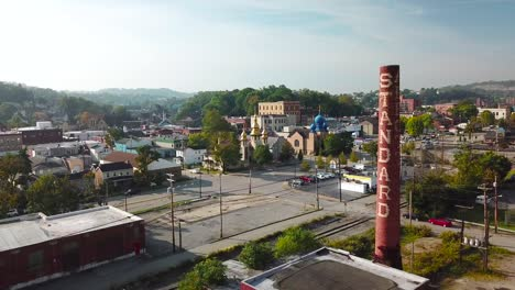 An-aerial-around-an-industrial-American-town-abandoned-smokstack-with-Ukranian-Orthodox-church-background