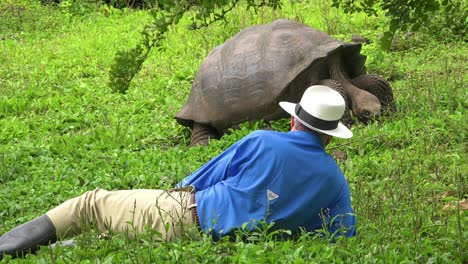 A-tourist-lies-on-the-ground-admiring-a-giant-land-tortoise-in-the-Galapagos-Islands-Ecuador