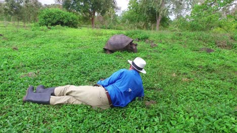 Traveling-shot-of-a-tourist-lying-on-the-ground-admiring-a-giant-land-tortoise-in-the-Galapagos-Islands-Ecuador-1
