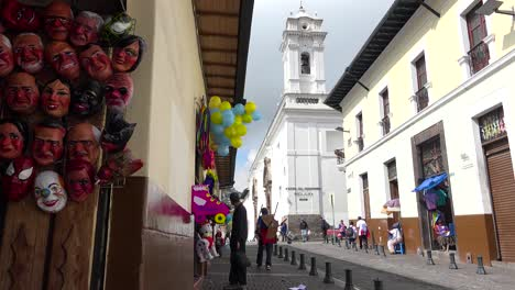 Pedestrians-walk-on-the-cobblestone-streets-of-Quito-Ecuador-with-pigeons-foreground-1