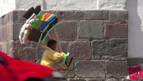A-man-carries-a-large-selections-of-brooms-down-a-street-in-Quito-Ecuador