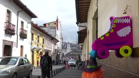 Pedestrians-walk-on-the-cobblestone-streets-of-Quito-Ecuador-with-pinata-foreground