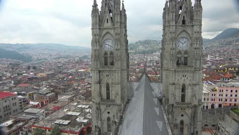 Pan-across-rooftop-shot-of-the-Basicala-Del-Voto-Nacional-in-Quito-Ecuador-with-city-background