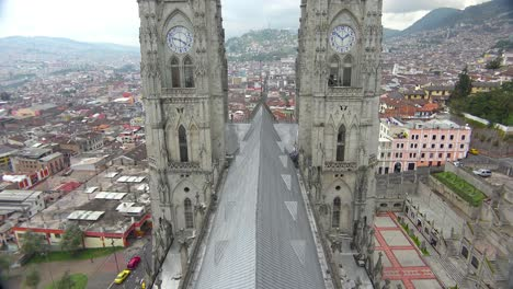 Tilt-up-rooftop-shot-of-the-Basicala-Del-Voto-Nacional-in-Quito-Ecuador-with-city-background