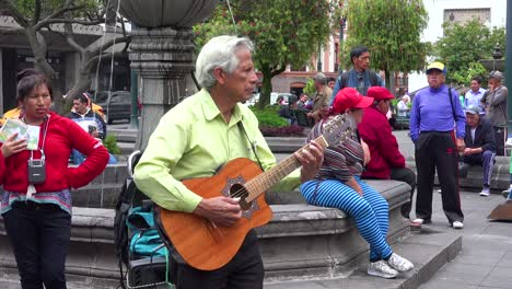 A-man-plays-guitar-in-a-park-in-downtown-Quito-Ecuador-udring-lunch-hour