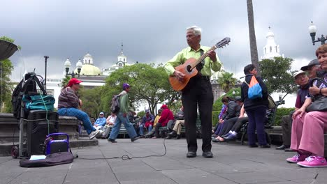 A-man-plays-guitar-in-a-park-in-downtown-Quito-Ecuador-udring-lunch-hour-1
