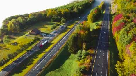 Aerial-of-a-car-traveling-on-a-highway-through-the-fog-in-fall