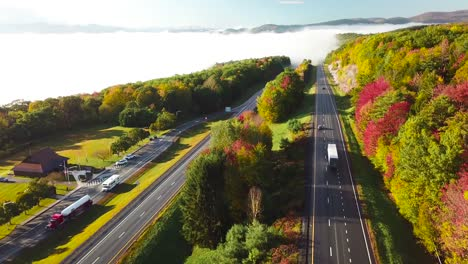 Aerial-of-a-semi-truck-traveling-on-a-highway-road-through-the-fog-in-fall