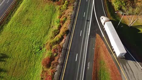 Aerial-of-a-semi-truck-traveling-on-a-highway-road-through-the-fog-in-fall-1