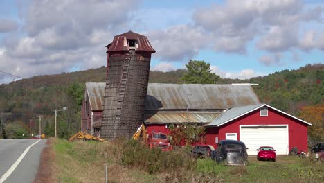 Old-cars-sit-outside-beside-a-red-barn-along-a-rural-road-in-Vermont
