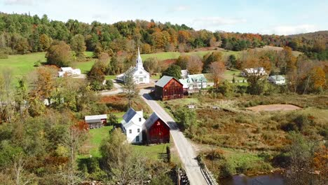 An-aerial-over-a-charming-small-village-scene-in-Vermont-with-church-road-and-farm-3