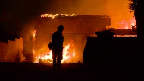 Ein-Feuerwehrheld-Geht-Vor-Einem-Brennenden-Gebäude-Das-Einstürzt