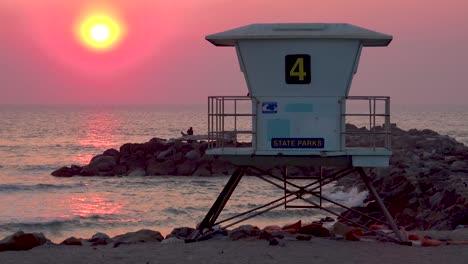 A-sunset-behind-a-lifeguard-station-along-a-California-beach