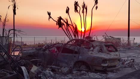 Burned-cars-smolder-at-sunset-beside-a-hillside-house-following-the-2017-Thomas-fire-in-Ventura-County-California
