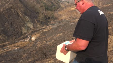 A-man-rolls-block-fo-salt-into-a-burned-canyon-to-help-feed-wildlife-displaced-by-the-Thomas-wildfire-in-2017